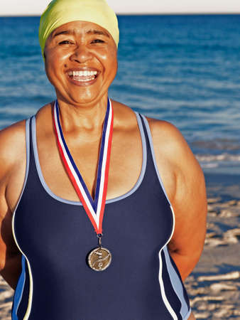prevailing: Mixed Race woman with medal on beach
