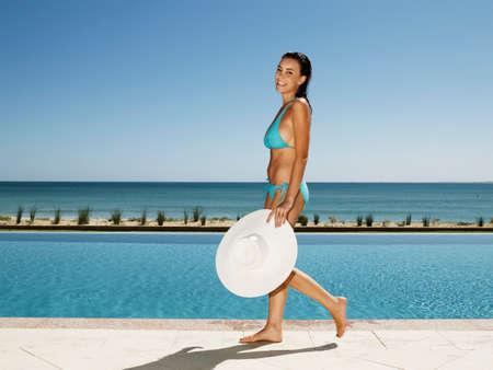 dangling: Hispanic woman walking next to swimming pool LANG_EVOIMAGES