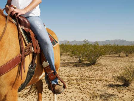 bathingsuit: Hispanic woman riding horse LANG_EVOIMAGES