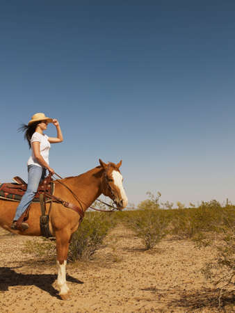 three persons only: Hispanic woman riding horse LANG_EVOIMAGES