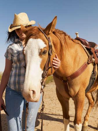 full length herbivore: Hispanic woman standing next to horse