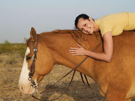 full length herbivore: Hispanic woman hugging horse LANG_EVOIMAGES