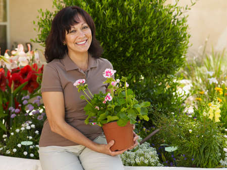 jointly: Hispanic woman holding potted plant