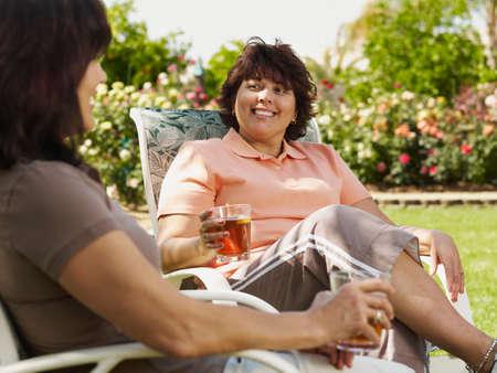 exerting: Hispanic women sitting in deck chairs LANG_EVOIMAGES