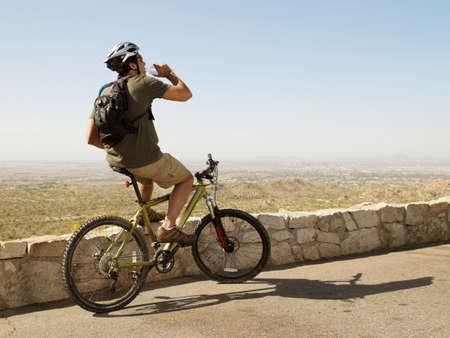 ceasing: Hispanic man drinking water on bicycle