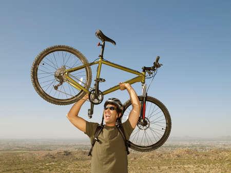 ceasing: Hispanic man holding bicycle over head