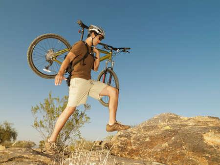 ceasing: Hispanic man carrying bicycle