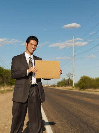 roadside stand: Hispanic businessman holding blank sign