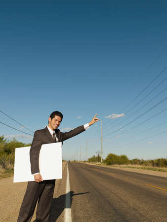 Hispanic businessman holding blank sign