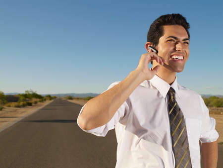 handsfree device: Hispanic businessman using hands-free device