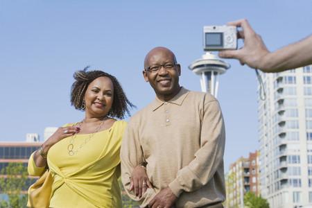 sidewalk talk: African American couple having photograph taken