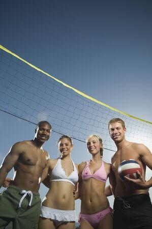 Multi-ethnic friends under beach volleyball net
