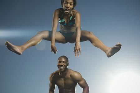 bathingsuit: African American woman in bathing suit jumping over man
