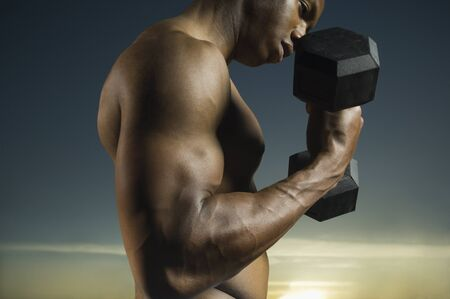 low spirited: African American man lifting weights