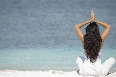bathingsuit: Hispanic woman practicing yoga at beach