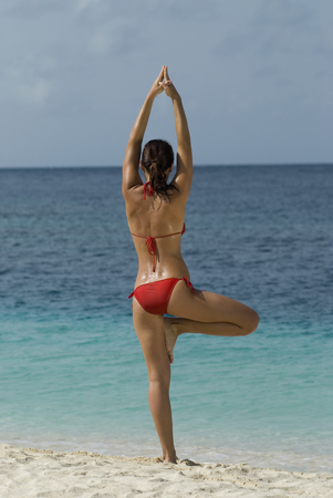 Young woman practicing yoga at beach LANG_EVOIMAGES