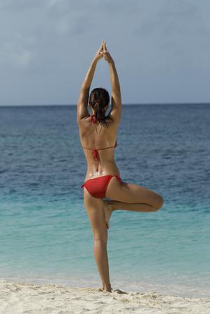 Young woman practicing yoga at beach Stok Fotoğraf