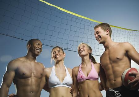 connexion: Multi-ethnic friends under beach volleyball net