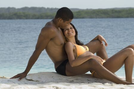 mate married: Hispanic couple sitting on beach LANG_EVOIMAGES