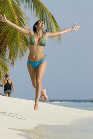ceasing: Hispanic woman jumping on beach