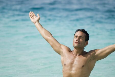 bathingsuit: Hispanic man with arms outstretched at beach
