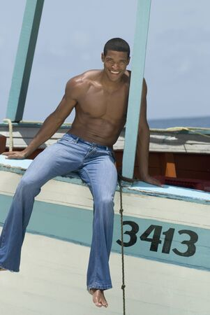 bathingsuit: Hispanic man sitting on boat LANG_EVOIMAGES