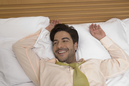 wearying: Hispanic businessman laying in bed