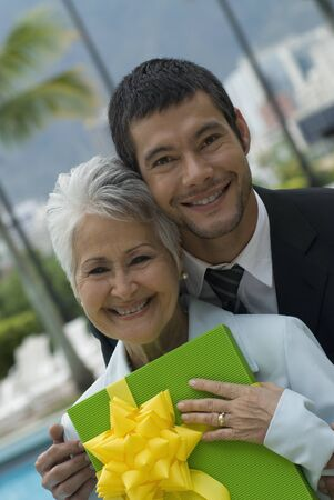 conferring: Hispanic man giving gift to mother