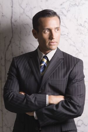 nite: Hispanic businessman with arms crossed LANG_EVOIMAGES