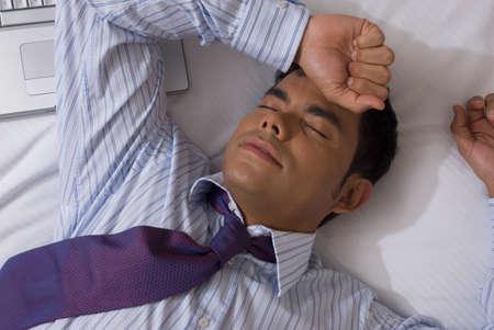 devilment: Hispanic businessman laying on bed