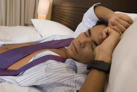 wearying: Hispanic businessman sleeping on bed