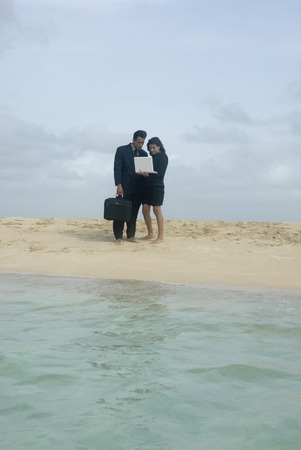 ceasing: Hispanic businesspeople with laptop at beach LANG_EVOIMAGES