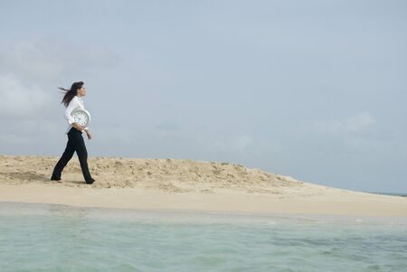 Woman carrying clock at beach LANG_EVOIMAGES