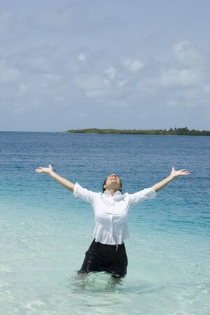 Hispanic businesswoman in water with arms raised