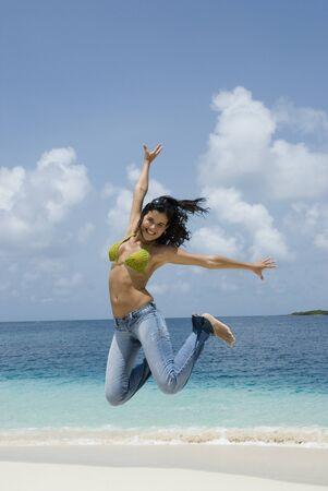 Hispanic woman jumping at beach Stock Photo