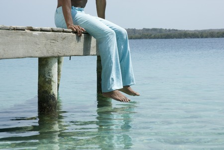 Hispanic man sitting on dock