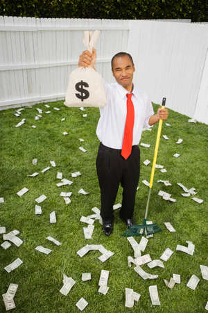 jeopardizing: Mixed Race businessman raking up money LANG_EVOIMAGES
