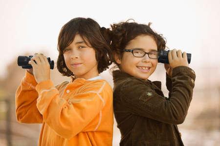 Hispanic brother and sister holding binoculars Stock Photo