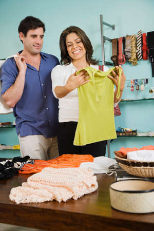 enquiring: Hispanic couple shopping in clothing store LANG_EVOIMAGES