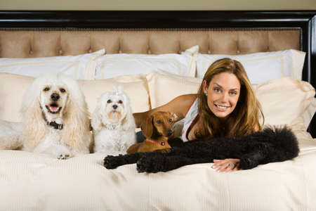 imploring: Hispanic woman laying on bed with dogs