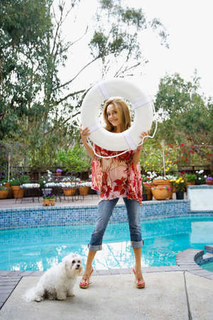 life preserver: Hispanic woman holding life preserver next to swimming pool LANG_EVOIMAGES