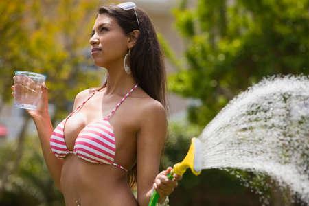 attired: Hispanic woman in bikini watering plants