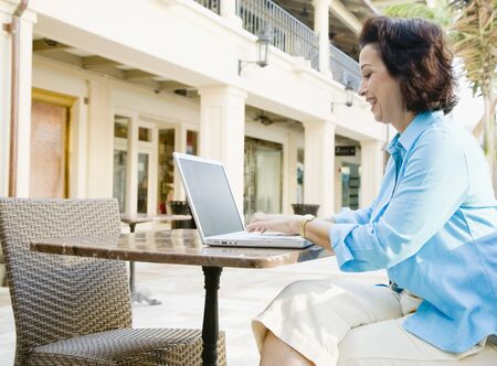cashpoint: Hispanic woman typing on laptop