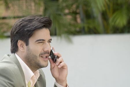 wearying: Hispanic businessman talking on cell phone