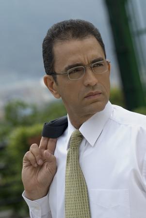interrogating: Hispanic businessman with jacket over shoulder