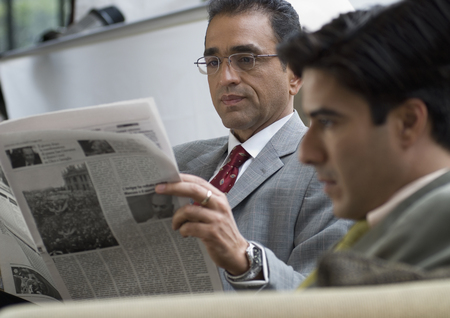 gusto: Hispanic businessman reading newspaper LANG_EVOIMAGES