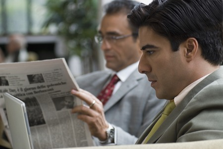 conferring: Hispanic businessman reading newspaper LANG_EVOIMAGES