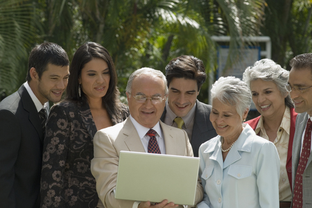 two persons only: Group of Hispanic businesspeople looking at laptop LANG_EVOIMAGES
