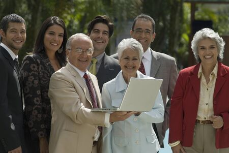 conferring: Group of Hispanic businesspeople with laptop