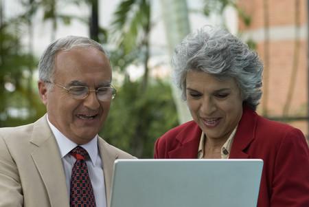 freeing: Senior Hispanic couple looking at laptop LANG_EVOIMAGES